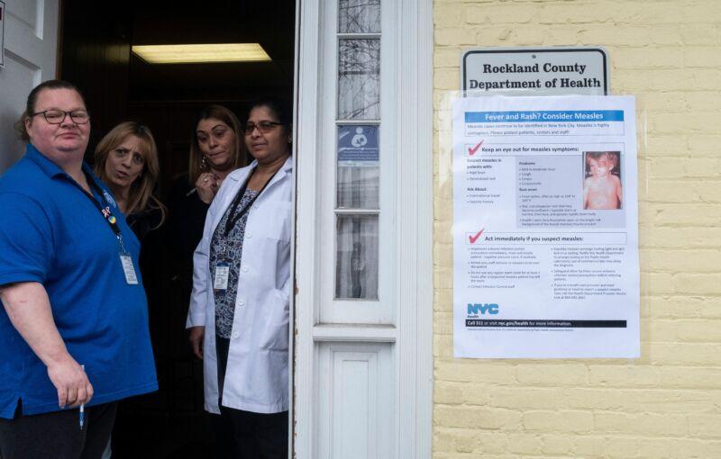 Women stand in a doorway.