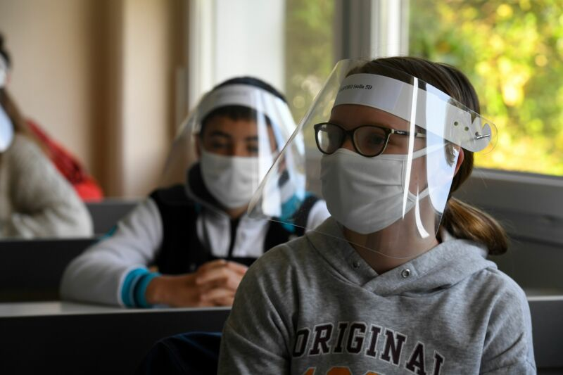 Children sit at desks while wearing clear masks.