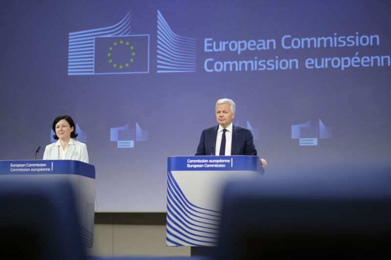 A man and a woman stand at podiums in front of an EU logo.