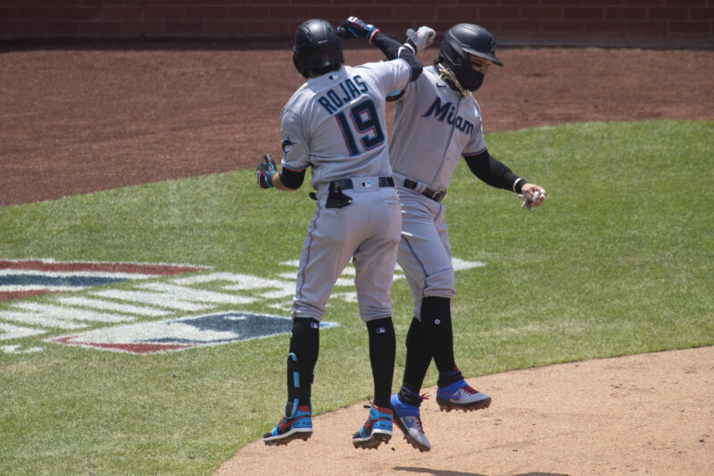Swapping elbow bumps for high-fives and adding some mask use among players was not enough to prevent an outbreak of COVID-19 among the Miami Marlins. (Miami players Miguel Rojas and Isan Diaz celebrating during a game against the Phillies, July 26, 2020 in Philadelphia.)
