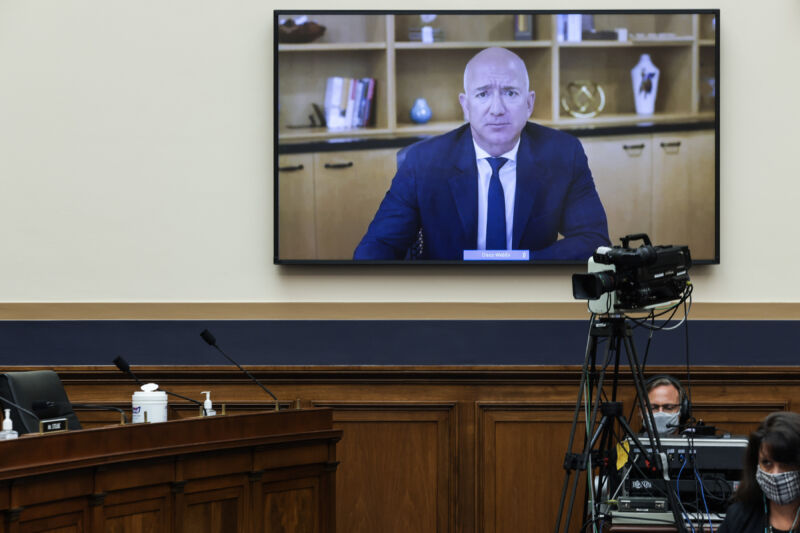 A man on TV addresses the legislators' room.