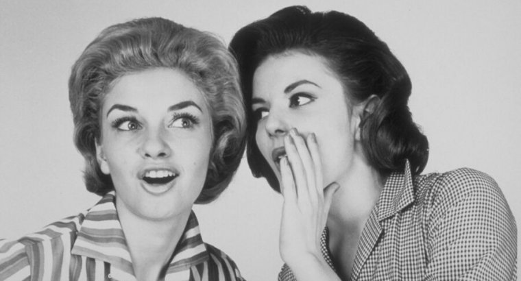Black-and-white photo of two 1950s style women whispering.