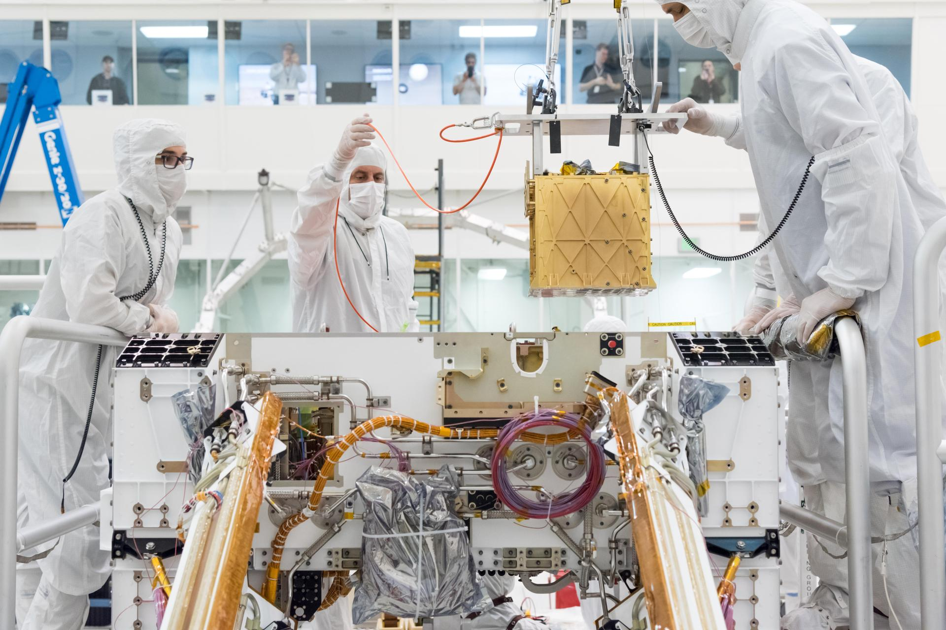 Members of NASA's Mars 2020 project install the Mars Oxygen In-Situ Resource Utilization Experiment (MOXIE) into the chassis of NASA's next Mars rover.