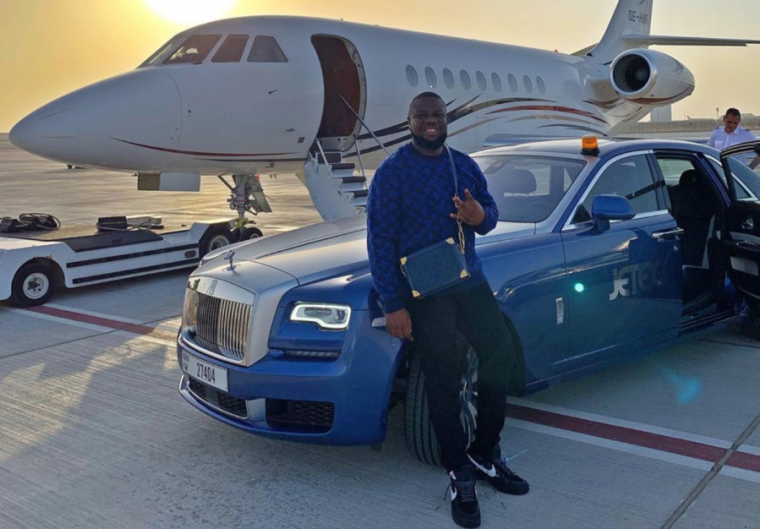 A smiling man leans against an expensive car parked in front of a private jet.