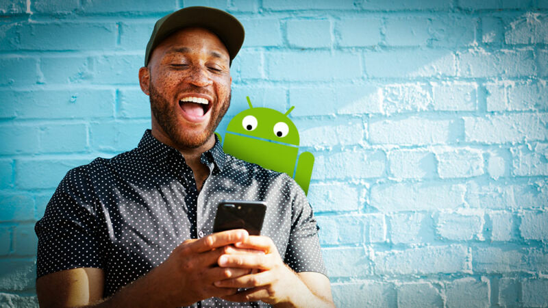 A man laughs at his smartphone while a cartoon characters peaks over his shoulder.