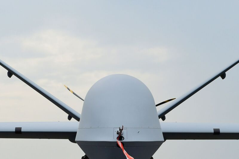 A military drone is faceless and menacing against a mostly blue sky.