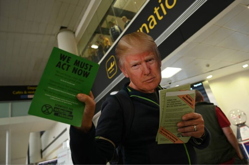 A climate activist wearing a mask of US President Donald Trump hands out leaflets at a protest action during the eleventh day of demonstrations by the climate change action group Extinction Rebellion, at Gatwick Airport, in Crawley, south of London on October 17, 2019. Activists from the environmental campaign group Extinction Rebellion have vowed to challenge a blanket protest ban imposed by the London police. (Photo by Glyn KIRK / AFP) (Photo by GLYN KIRK/AFP via Getty Images)