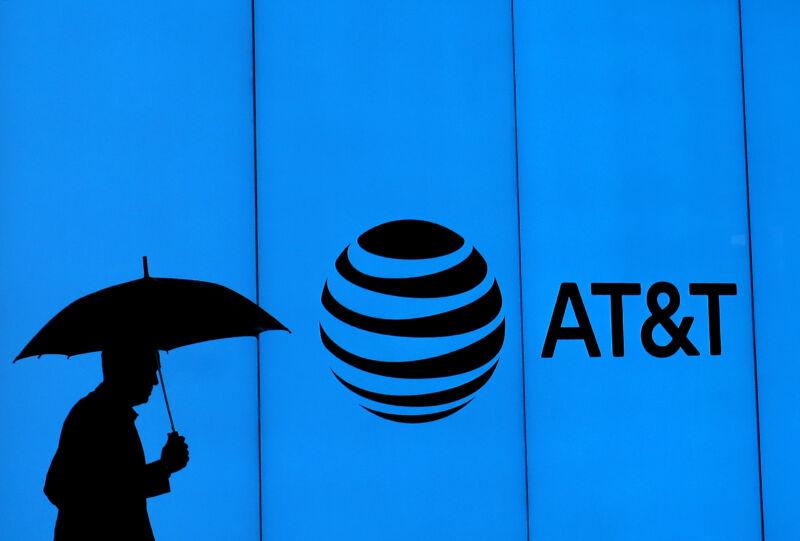 مردی با چتر از کنار ساختمانی با نشان AT&T عبور می کند.