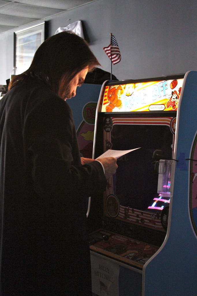 "Billy Mitchell reviews a document in front of a <em>Donkey Kong</em> machine decked out for the annual ""Kong Off"" high score competition."