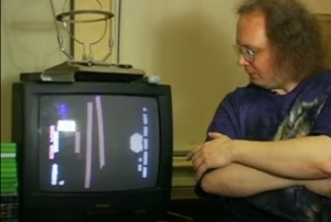 "Former Twin Galaxies referee Robert Mruczek sits next to taped footage of a Mitchell performance showing the telltale ""girder finger"" in a 2006 MTV News interview."