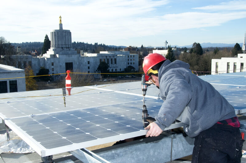 Workers in hardhats install rooftop solar panels.