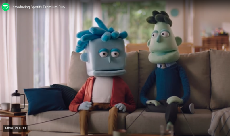 Screenshot from commercial features two puppets conversing on a sofa.