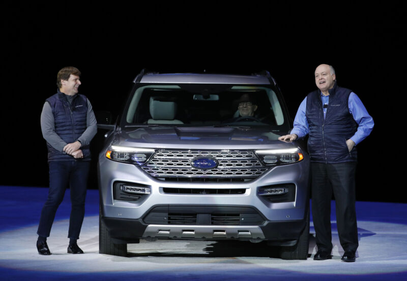 Two men in business casual stand next to an SUV.