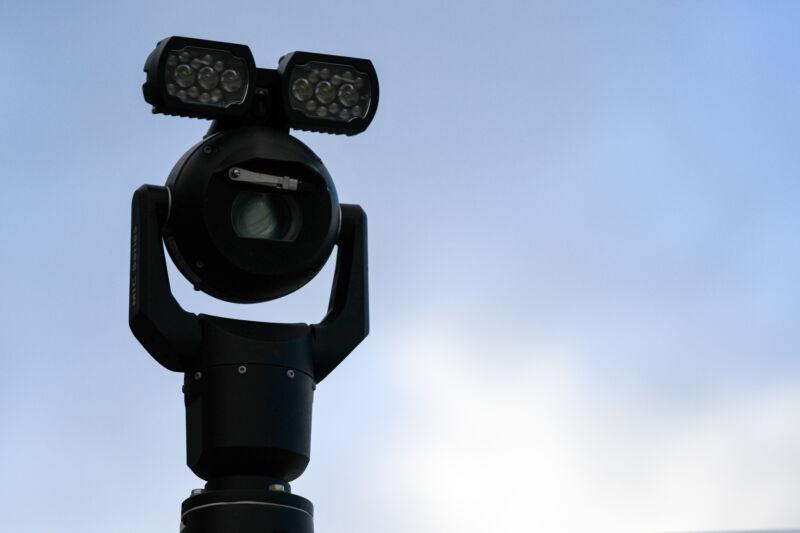 Vaguely menacing camera atop an outdoor metal post.