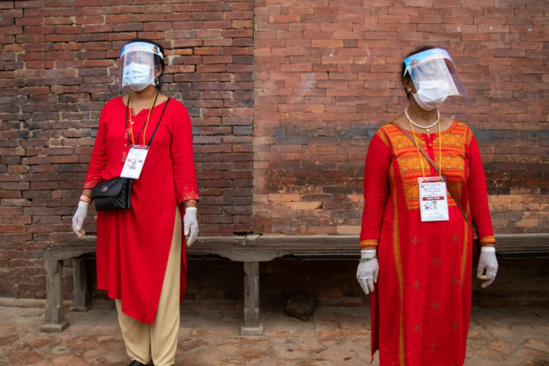 Image of two women wearing both face masks and face shields.