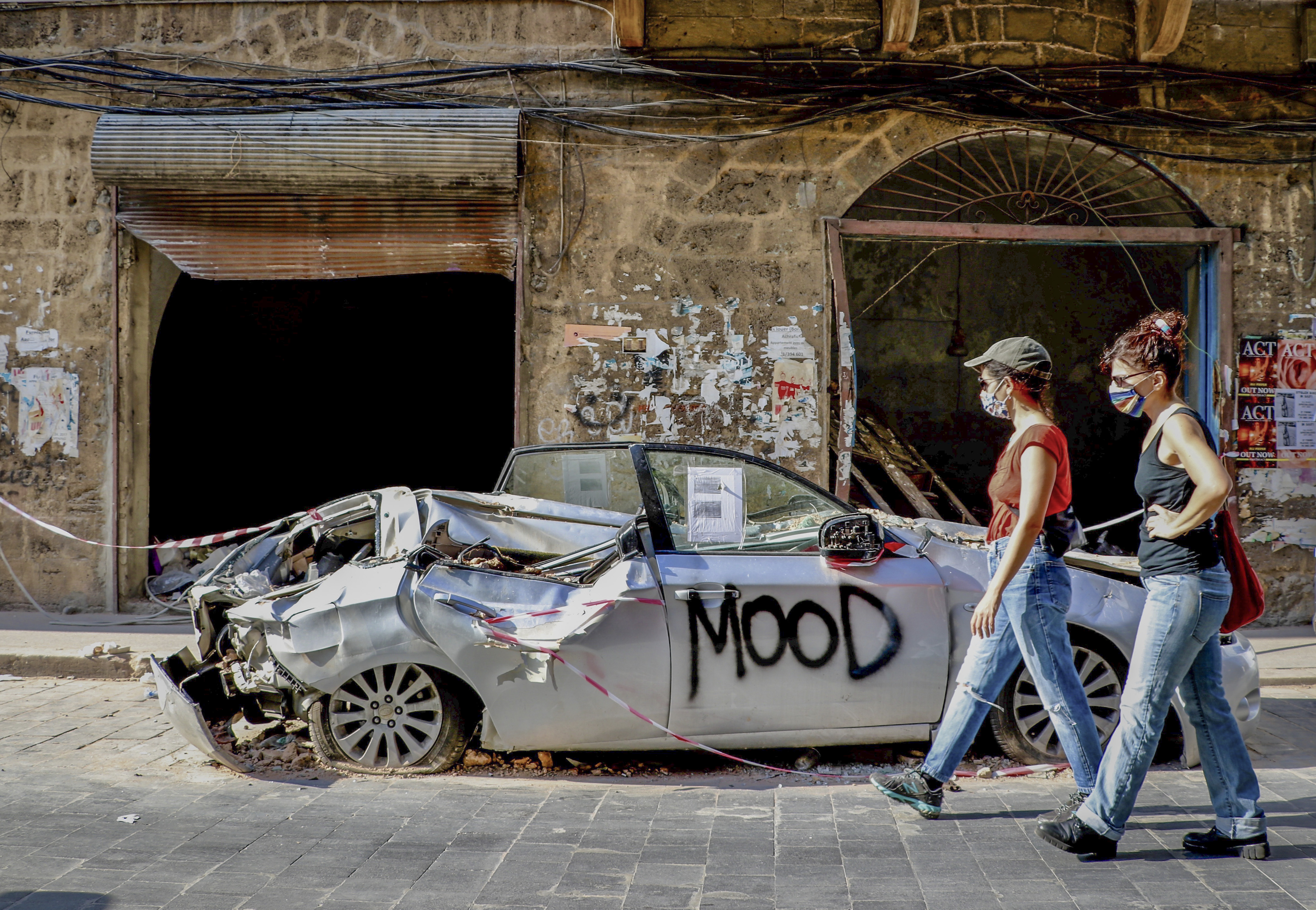 Women walk past a damaged car on August 13, a week-plus after the Port of Beirut explosions. Getty's suggested caption describes the streets of Beirut as