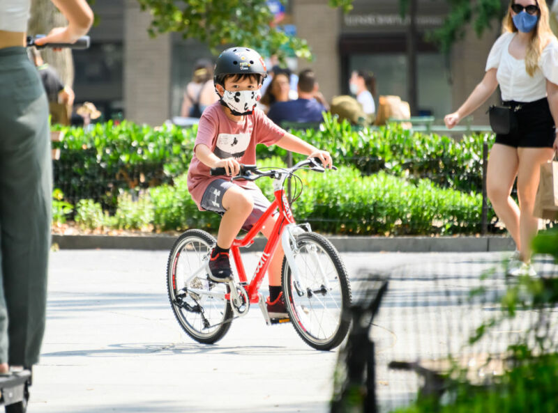 Image of a child wearing a face mask and riding a bicycle.