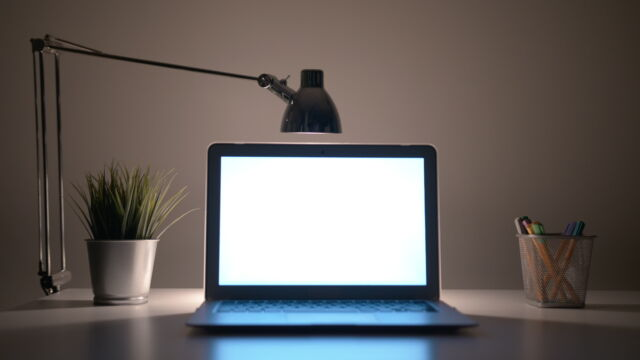 You definitely want that light <em>behind</em> your screen, not aimed at it. A bit of illumination behind and around the screen helps reduce eyestrain.