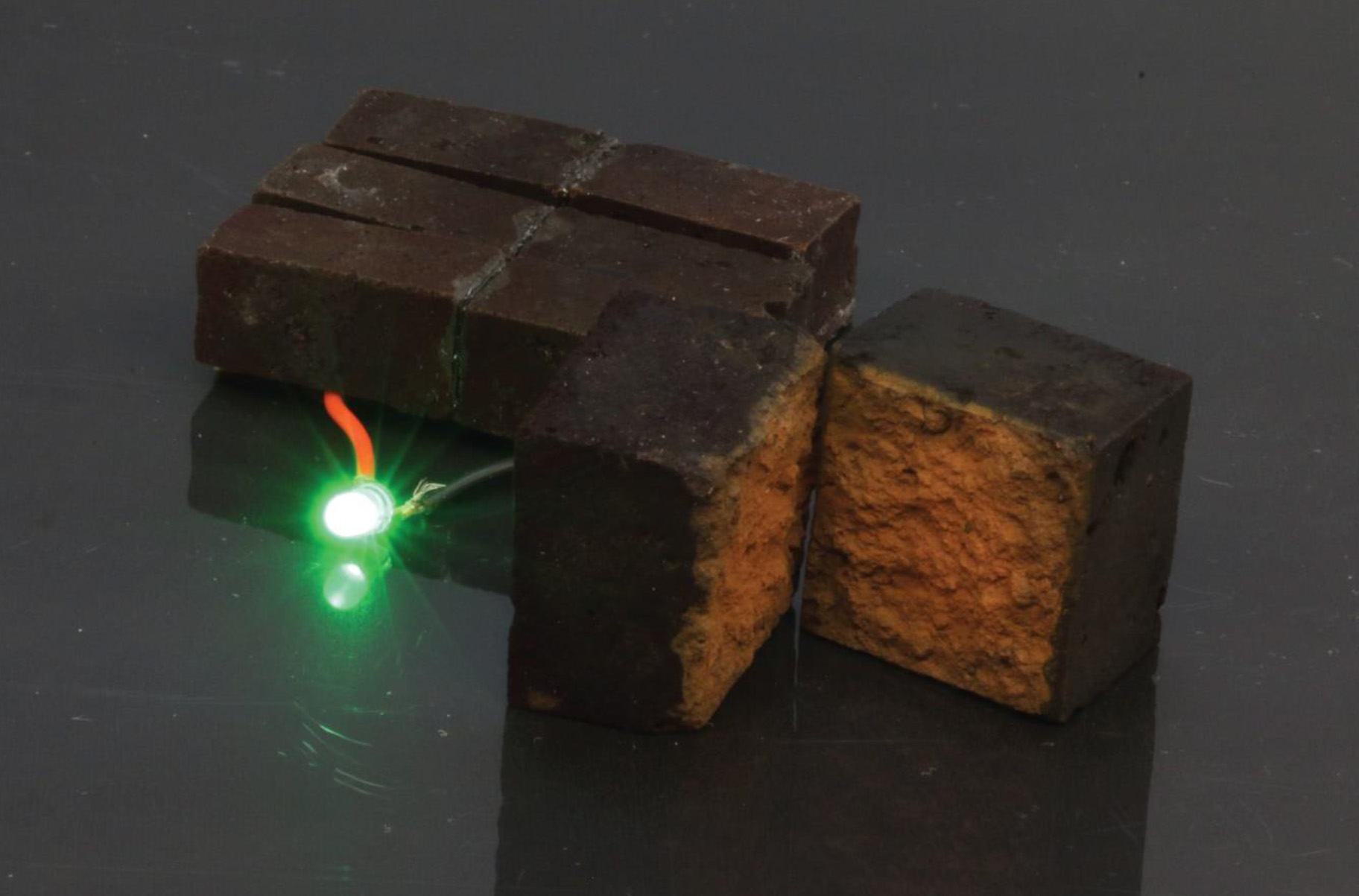 Three larger brick supercapacitors in series light an LED. The split brick on the right shows the color-change from the PEDOT coating.