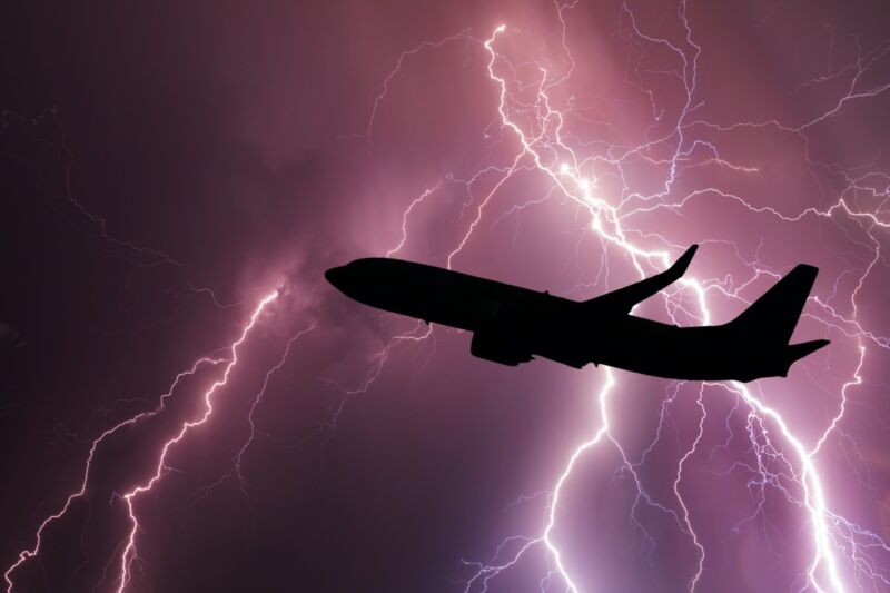 A passenger jet is gloriously silhouetted by a lightning storm.