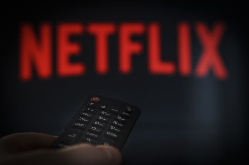 A person's hand holding a remote control in front of a TV screen with a Netflix logo.