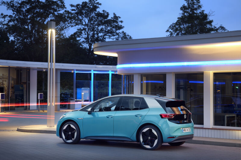 A turquoise Volkswagen ID.3 at dusk, surrounded by neon lights.