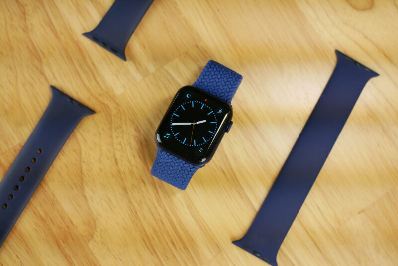 apple watch series 6 laying sideways on a table next to the sport band and solo loop band