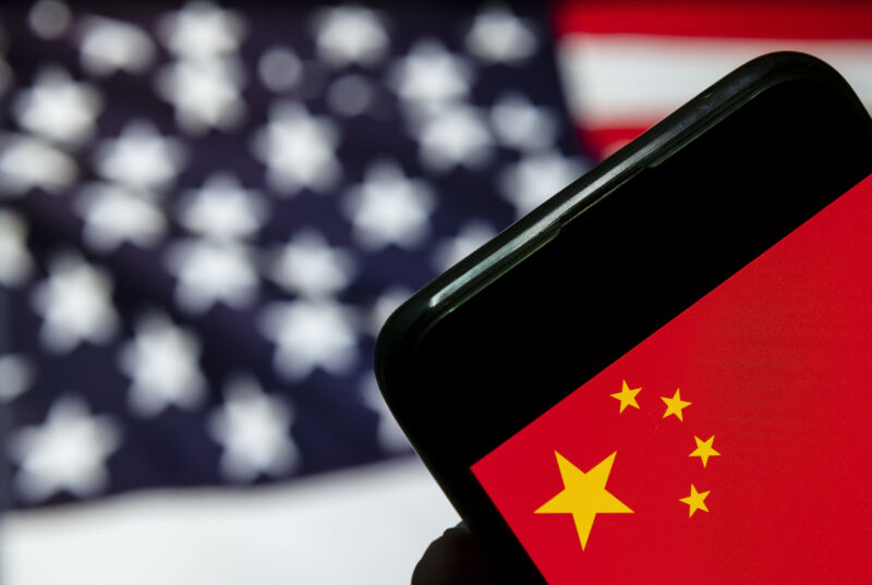 An American flag is out of focus behind a smartphone showing an image of the Chinese flag.