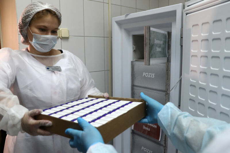 Image of a women in medical protective gear holding a box of samples.