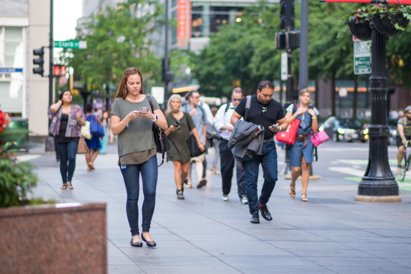 Stock photo of people on urban sidewalk walking and looking at smartphones.