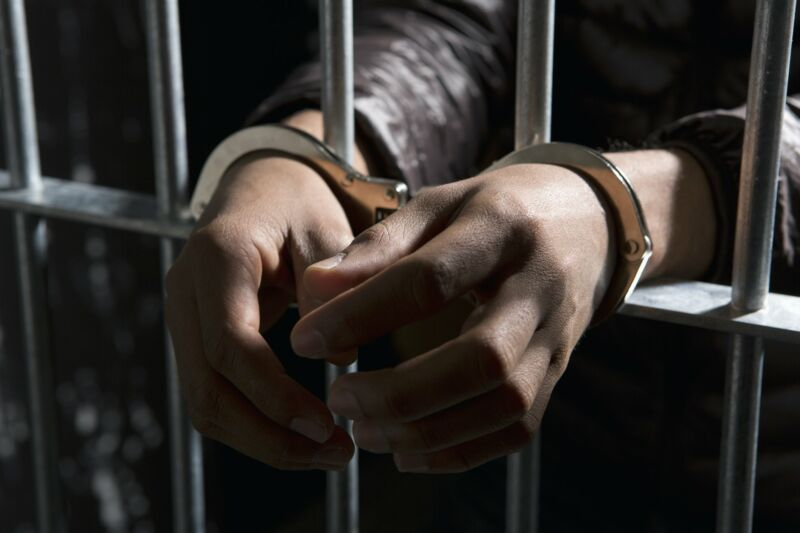 Picture of a jail cell in which a man's handcuffed hands are sticking out through the bars.