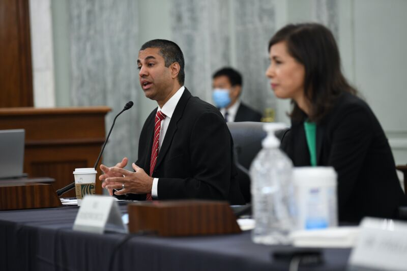 FCC Chairman Ajit Pai sitting at a table and speaking at a Senate hearing, with FCC Commissioner Jessica Rosenworcel also pictured.