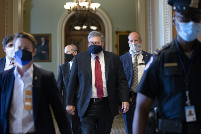 Attorney General William Barr walking down a hallway while wearing a mask.