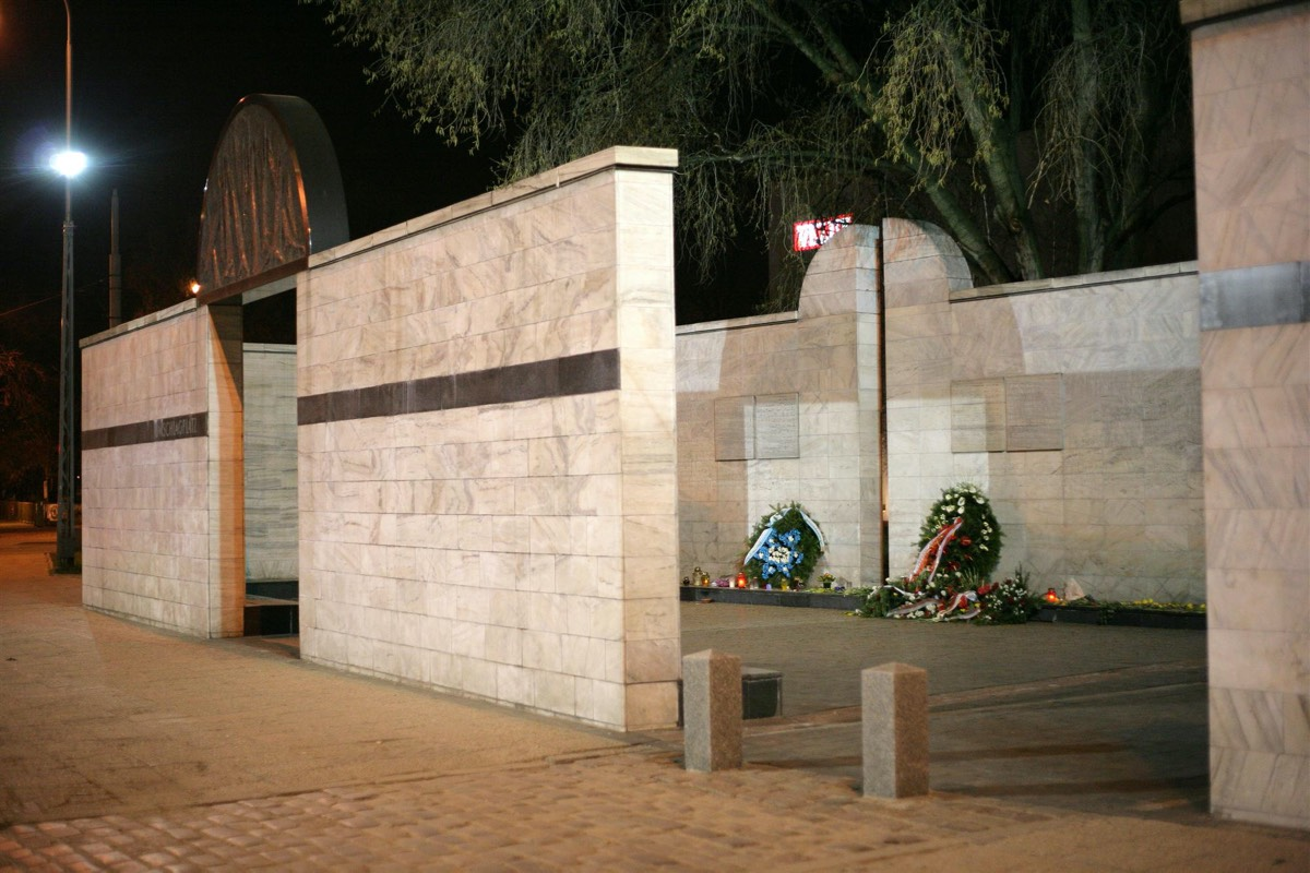 "National monument at the Ghetto's former <em>Umschlagplatz</em>—the term used to denote the holding areas adjacent to railway stations, where Jews from ghettos were assembled for deportation to Nazi death camps—symbolizing an open freight car. Stawki Street, Warsaw.""><img alt="