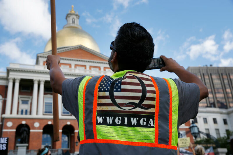 BOSTON—A man wearing a QAnon vest held a flag during a No Mandatory Flu Shot Massachusetts rally held outside of the State House in Boston on Aug. 30, 2020, to demonstrate against Gov. Charlie Baker's order for mandatory influenza vaccinations for all students under the age of 30, an effort to lower the burden on the health care system during the COVID-19 pandemic.