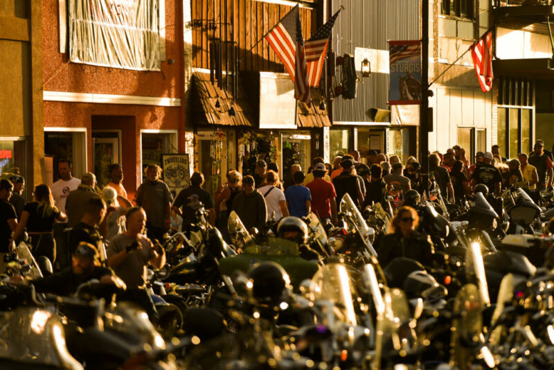 A small-town Main Street at night is cluttered with motorcycles and pedestrians.