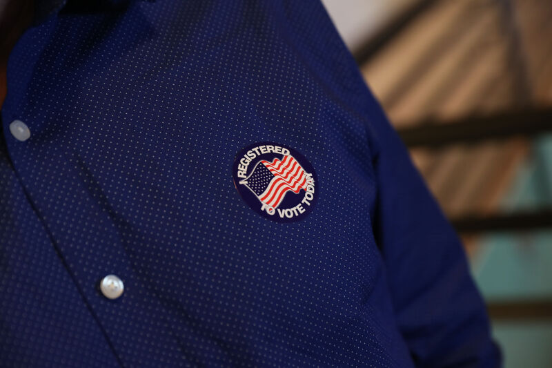Close-up photograph of a man's shirt with a sticker attached.