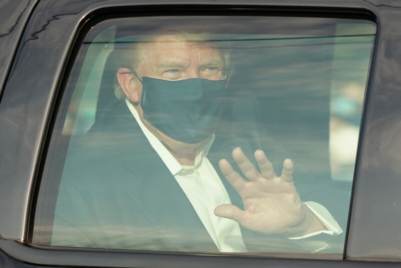 A masked man waves through a bulletproof window.