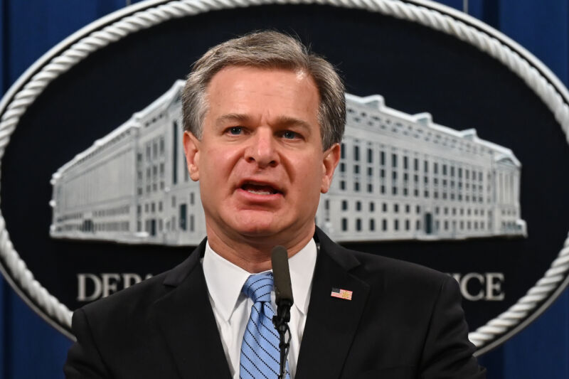 A man in a suit speaks in front of a Justice Department logo.