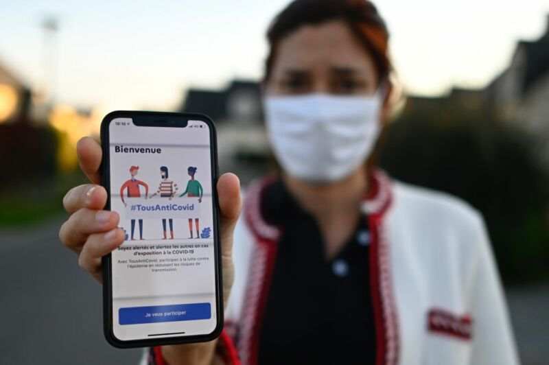 A woman in a face mask holds up a phone.