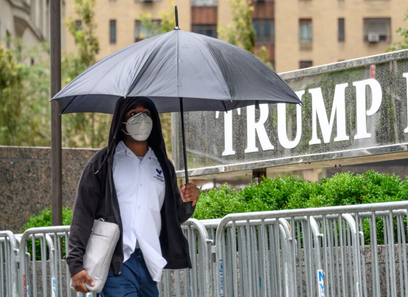 A person wears a protective face mask outside Trump International Hotel & Tower New York.