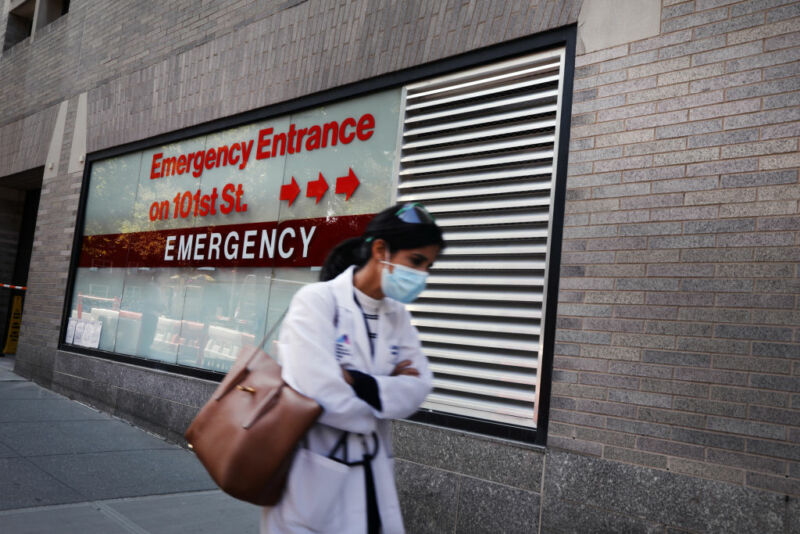 A doctor walking in front of the hospital entrance.