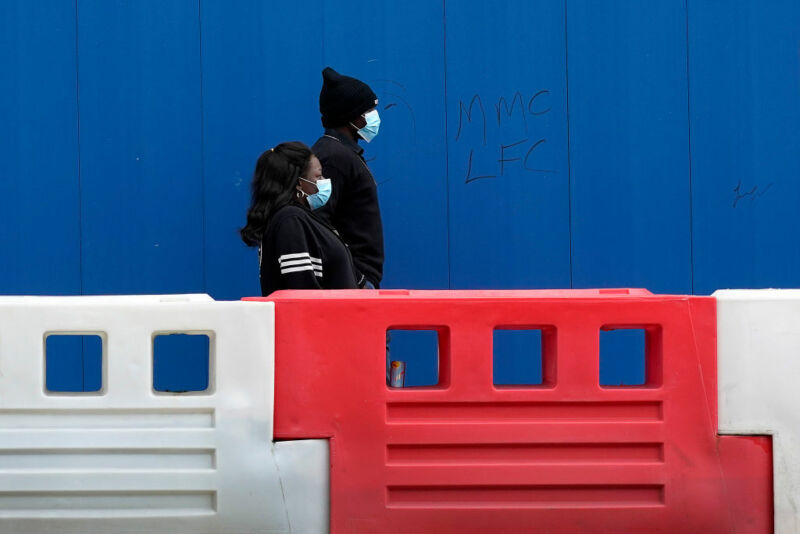 A masked man and woman walks outside a plastic barrier.