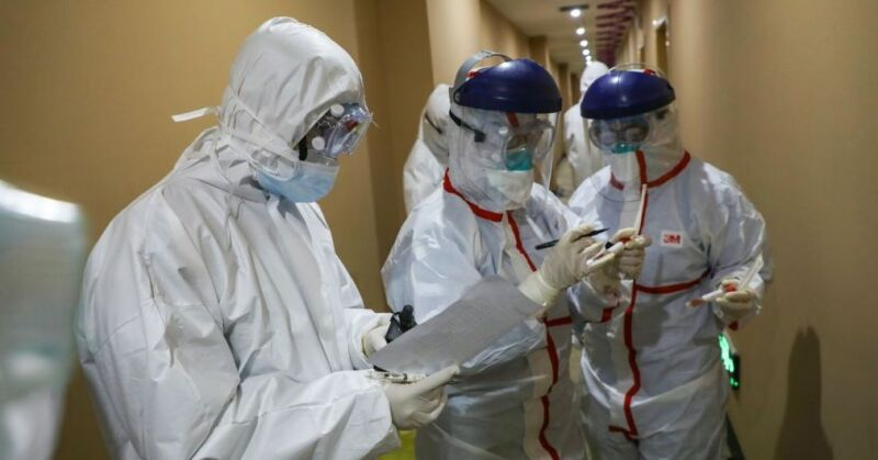 People in protective gear examine pages of notes.
