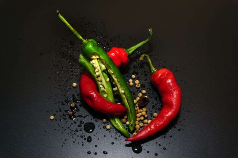 Seeds spill out of a trio of hot peppers in a skillet.