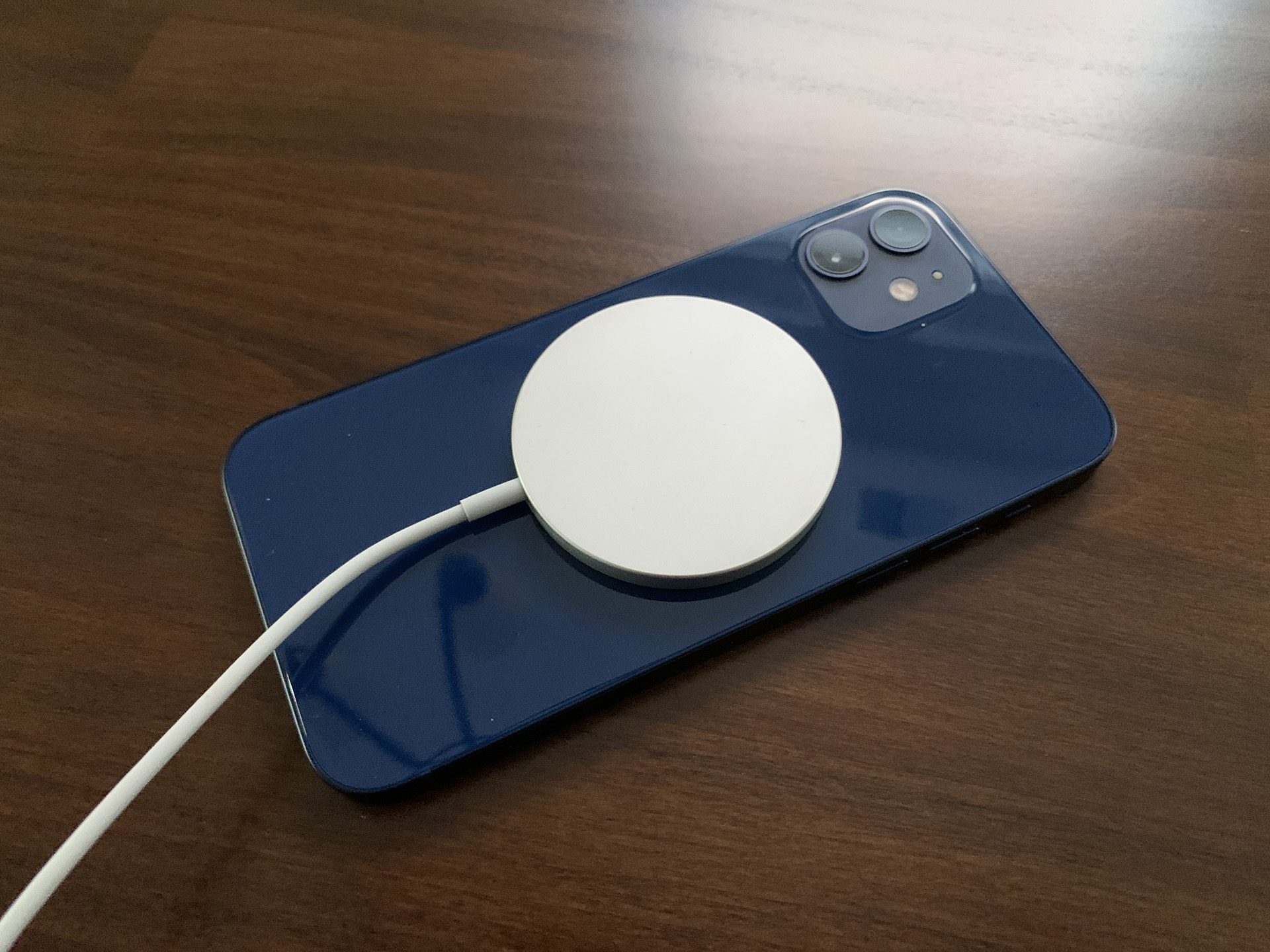 The Apple MagSafe charger attached to an iPhone 12.