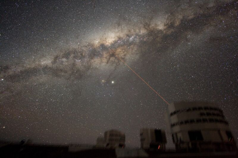 Image of the night sky above Paranal, Chile, on July 21, 2007, showing the galactic center of the Milky Way. The laser creates a guide-star for the telescope.