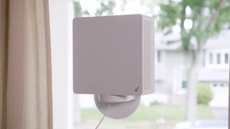 A Verizon 5G Home Internet device mounted on the inside of a window, at a home on a residential street.