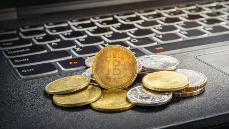 A pile of coins with the bitcoin logo sits atop a laptop keyboard.