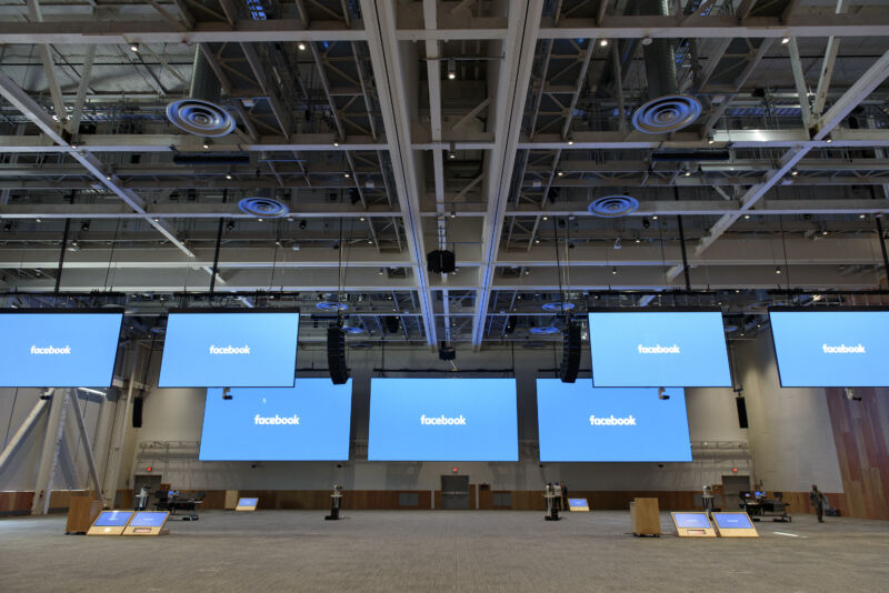 Giant monitors displaying the Facebook logo hang from the ceiling of an empty convention center.